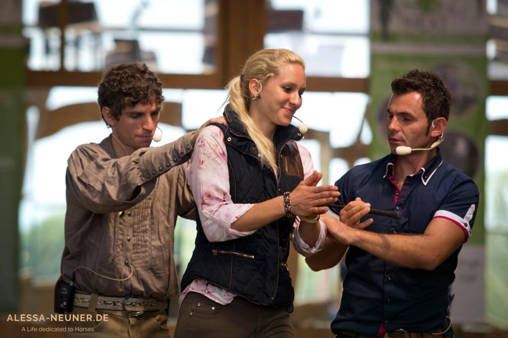 """Voller Körpereinsatz bei den drei Pferdemenschen: Miron funktioniert kurzerhand seine Kollegen zu einem """"Beispiels-Pferd"""" um und erklärt dem lachenden Publikum seine Idee. Die drei Trainer ergänzen sich wunderbar und jeder liefert auf seine Art spannenden Input."""